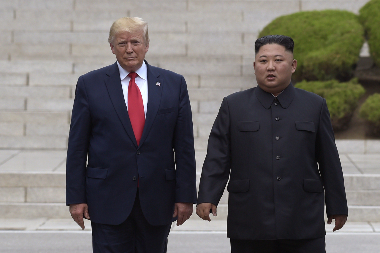 In this June 30, 2019, file photo, US President Donald Trump, left, meets with North Korean leader Kim Jong-un at the North Korean side of the border at the village of Panmunjom in Demilitarized Zone. North Korea says it is rethinking whether to abide by its moratorium on nuclear and missile tests and other steps aimed at improving ties with the US. (AP-Yonhap)