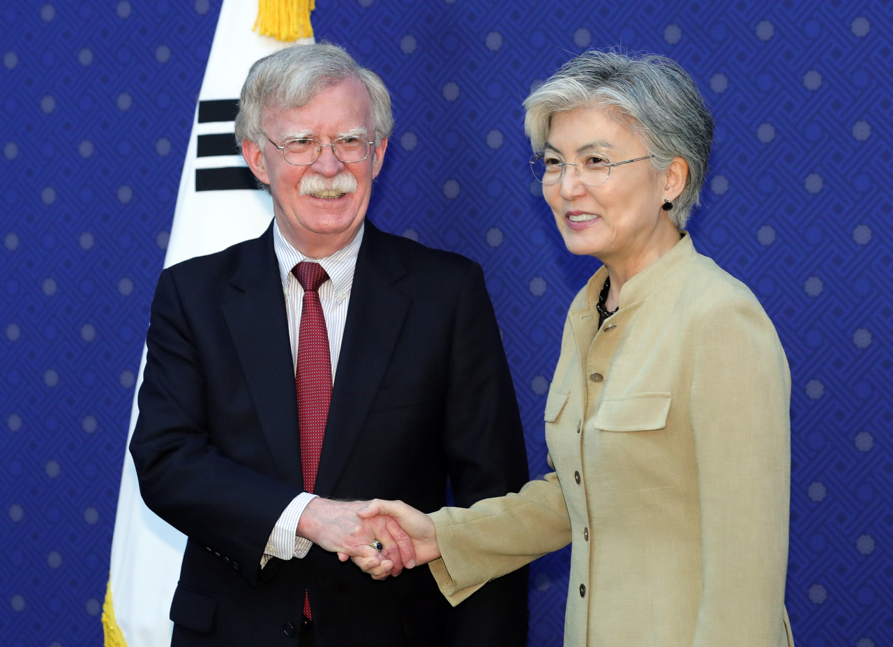 Foreign Minister Kang Kyung-hwa shakes hands with US national security adviser John Bolton at the Foreign Ministry office in Seoul, Wednesday. (Yonhap)
