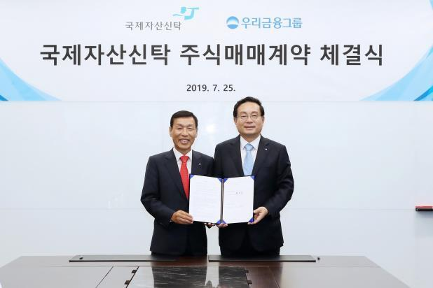 Son Tae-seung (right), chairman of Woori Financial Group and CEO of Woori Bank, pose for a photo next to Yoo Jae-eun, chairman of Kukje Asset Trust, on Friday. (Woori Financial Group)