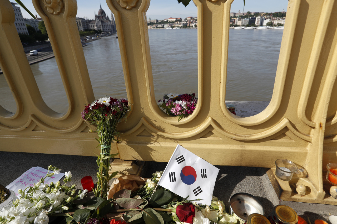 In this June 1 file photo, flowers and flag of South Korea are laid on the Margit Bridge where a sightseeing boat capsized in Budapest, Hungary. (AP-Yonhap)