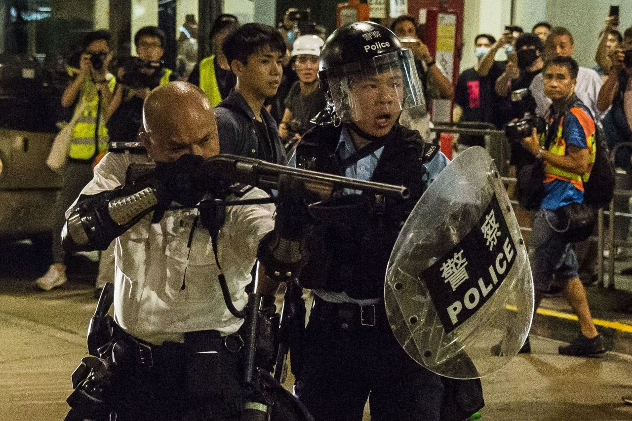 A police officer (left) points a firearm during a clash with protesters who had gathered outside Kwai Chung police station, in support of protesters detained with the charge of rioting, in Hong Kong (AFP)