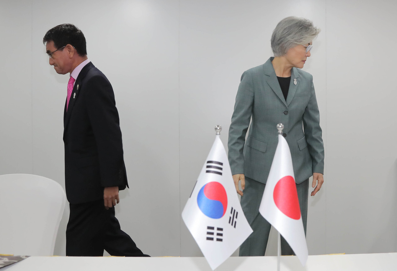 South Korea's Minister of Foreign Affairs Kang Kyung-wha (right) heads back to her seat after a photo session with Japanese counterpart Taro Kono in Bangkok on Thursday. (Yonhap)