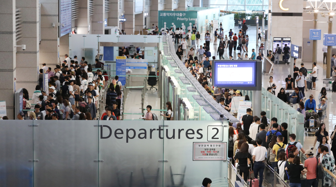Travelers are seen lining up near a departure gate at Incheon Airport on Wednesday. (Yonhap)