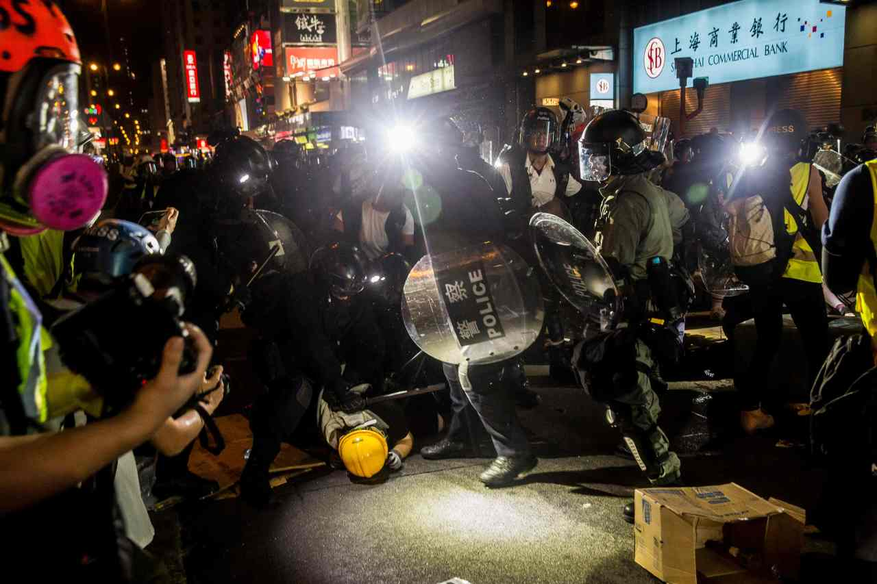 Hong Kong's riot police arrest pro-democracy protesters in the popular shopping district of Mong Kok on Saturday. (Yonhap)