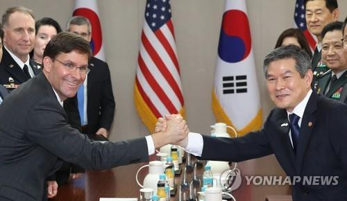 South Korean Defense Minister Jeong Kyeong-doo (right) and U.S. Secretary of Defense Mark Esper clasp hands ahead of their talks at the defense ministry in Seoul on Friday. (Yonhap)