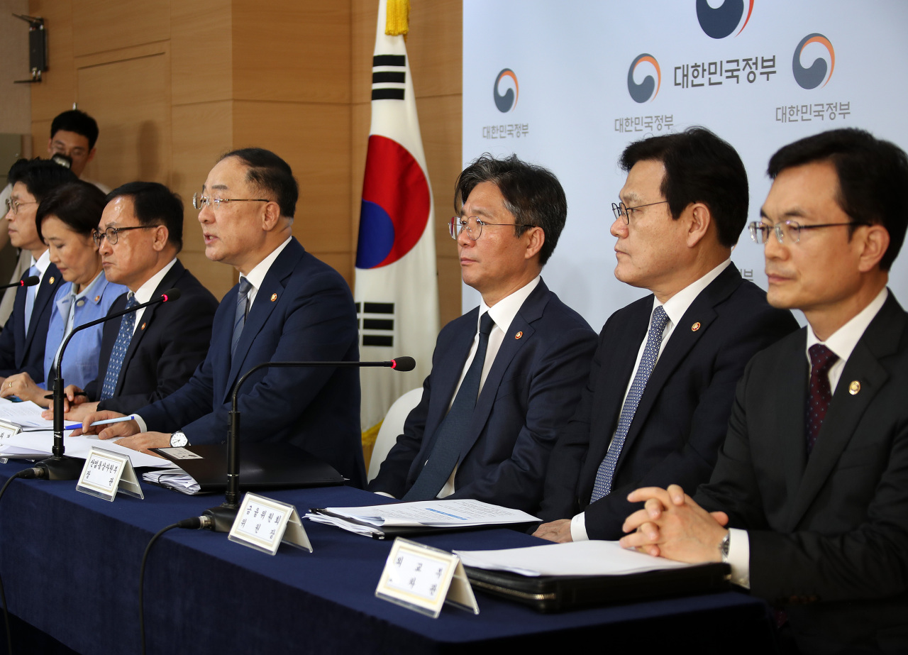 Deputy Prime Minister Hong Nam-ki (fourth from right) flanked by Trade Minister Sung Yun-mo (third from right), Financial Services Commission Chairman Choi Jong-ku (second from right), ICT Minister You Young-min (fifth from right) and SMEs Minister Park Young-sun (sixth from right) hold a press conference denouncing Japan's export curb move in Seoul on Aug. 2. (Yonhap)