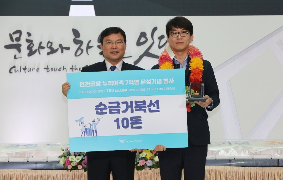IIAC CEO Koo Bon-hwan (left) poses with the 700 millionth passenger to arrive at Incheon Airport on Wednesday. (IIAC)