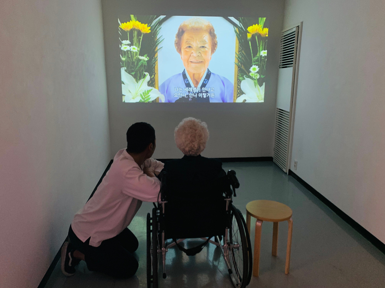 """Lee watches a video of her late friend Kim Gun-ja, a former """"comfort woman."""" Kim, who stayed in a room next to Lee's at the shelter, died in July 2017. Lee said Kim was like her """"other half."""" (Kim Arin/The Korea Herald)"""