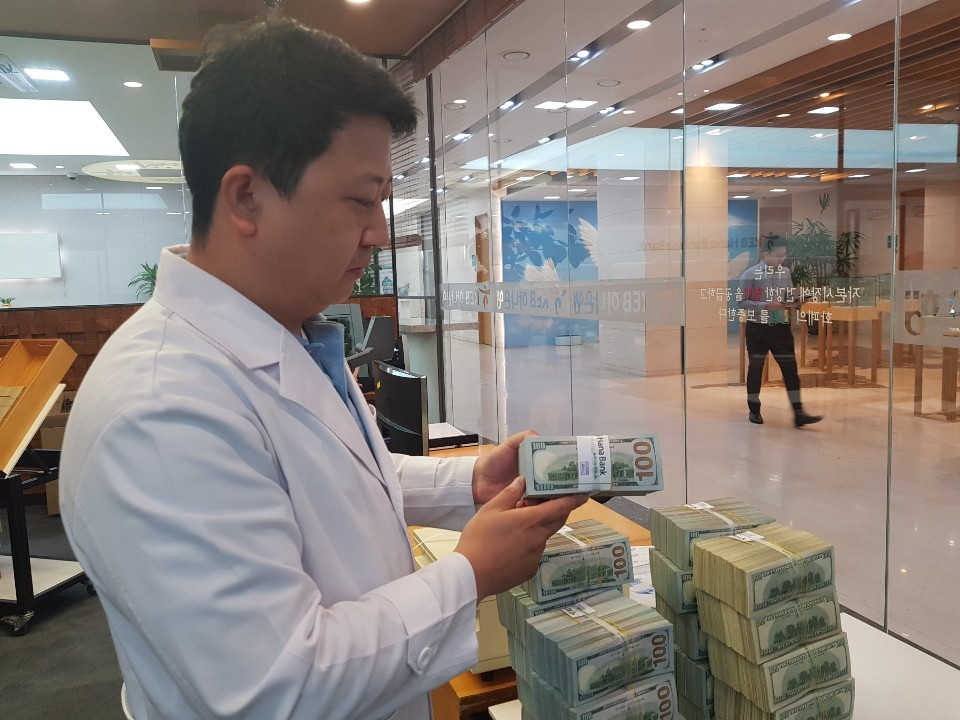 Yoo Hyun-chul, senior manager of KEB Hana Bank's anti-counterfeiting center, inspects stacks of $100 bills at the center. (Jung Min-kyung/The Korea Herald)