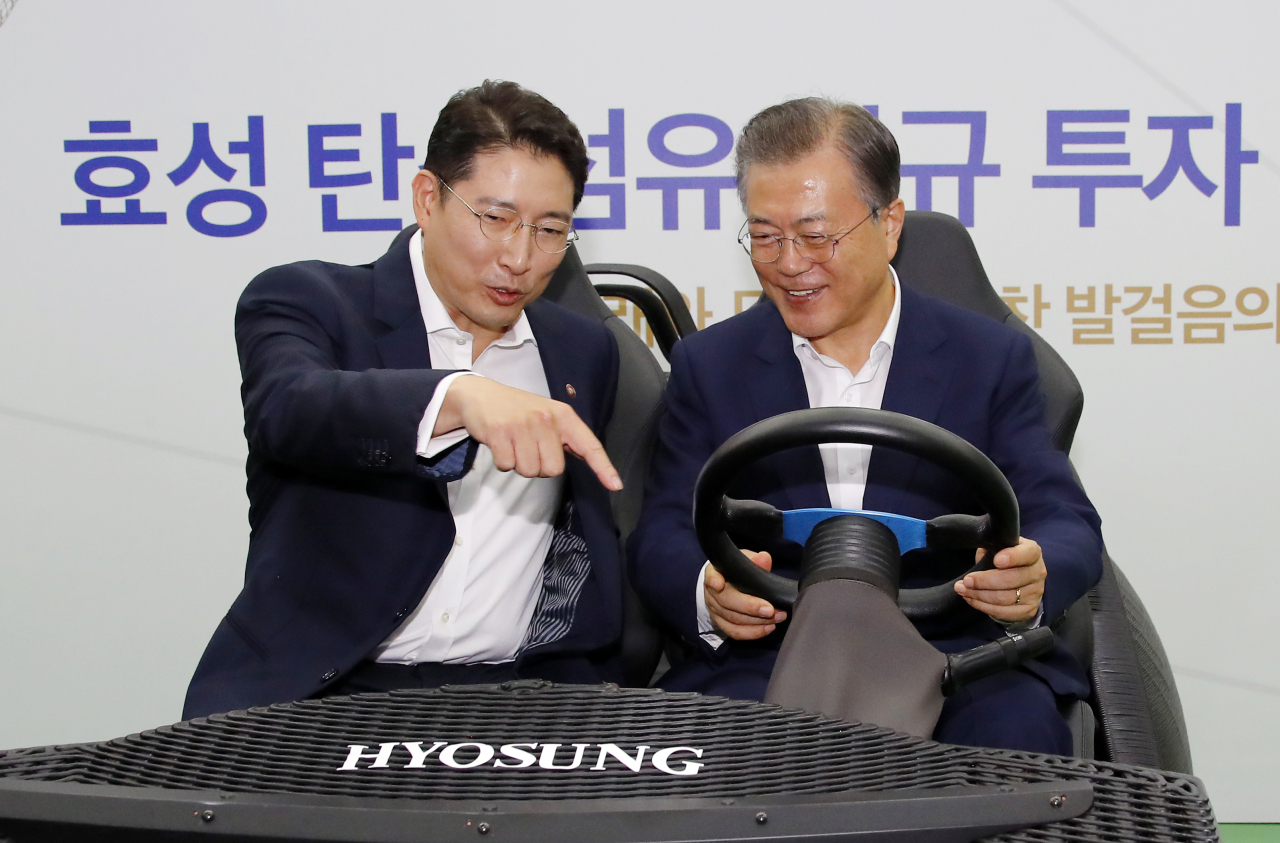 President Moon Jae-in and Hyosung Chairman Cho Hyun-joon take a 3D printed carbon fiber electric vehicle at Hyosung`s Jeonju plant on Tuesday. (Yonhap)