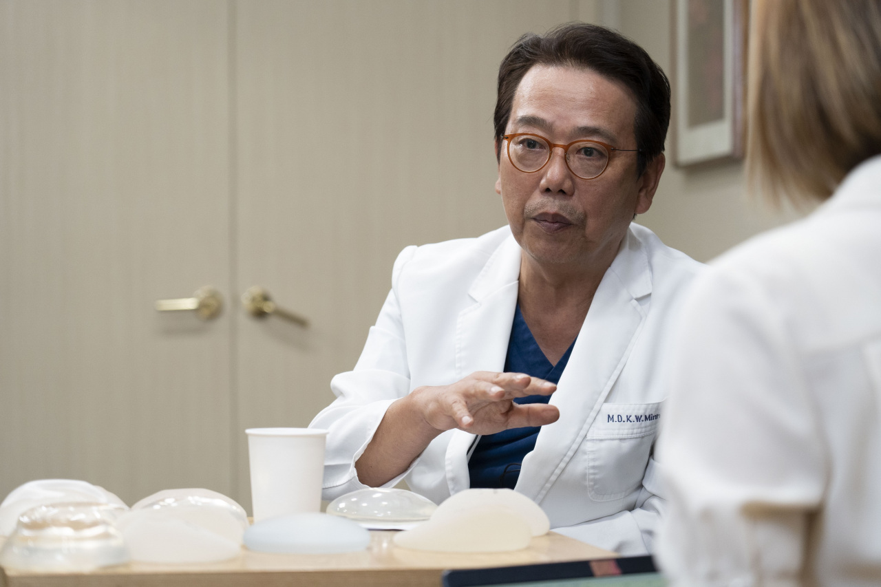 Minn Kyung-won, professor emeritus at Seoul National University Hospital, speaks to The Korea Herald. Types of breast implants are displayed on the table. (The Korea Herald)