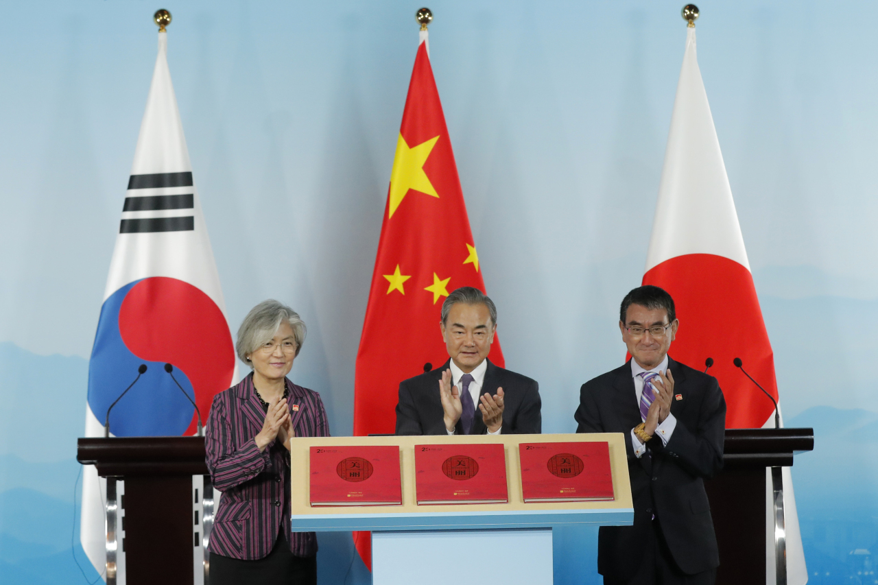 Chinese Foreign Minister Wang Yi, center, clap with his South Korean counterpart Kang Kyung-wha, left, and Japanese counterpart Taro Kono during a ceremony to launch a book after their trilateral meeting at Gubei Town in Beijing Wednesday. (AP-Yonhap)