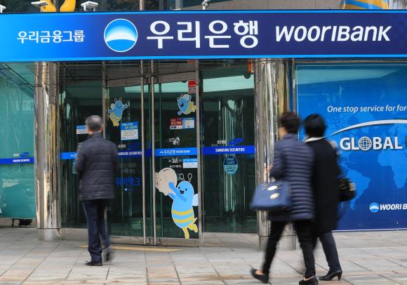 Customers enter a Woori Bank branch in Seoul (Yonhap)