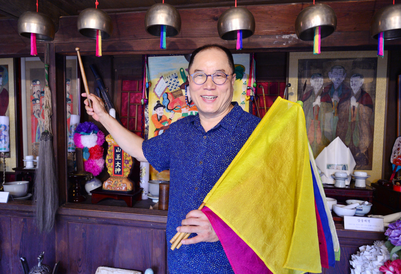 Yang Jong-sung explains the flags and bells used by shamans at the Museum of Shamanism in Seoul's Eunpyeong-gu district, Tuesday. (Park Hyun-koo/The Korea Herald)