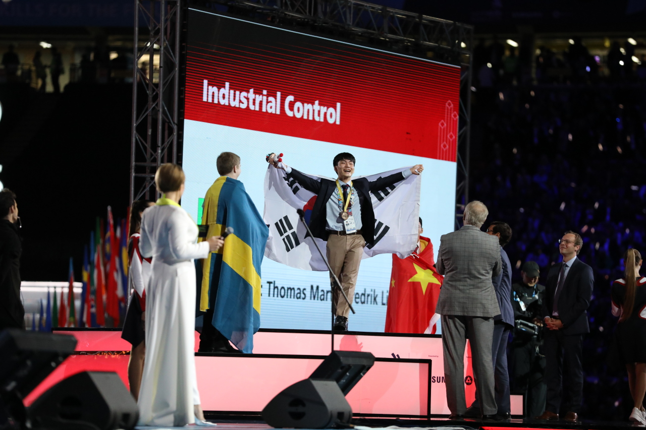 Yang Su-min (center) of Samsung Heavy Industries who won the gold medal in the Industrial Control category stands on the podium holding the South Korean national flag during the closing ceremony of the 45th WorldSkills Competition at Kazan Arena Stadium on Tuesday evening. (Human Resources Development Service of Korea)