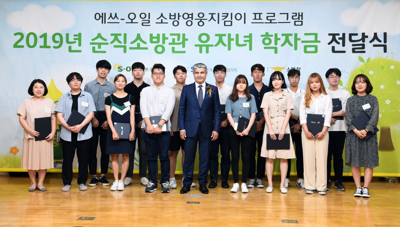 S-Oil CEO Hussain Al-Qahtani (center) takes a photo with children of fallen firefighters at Yongsan Fire Station on Tuesday. (S-Oil)
