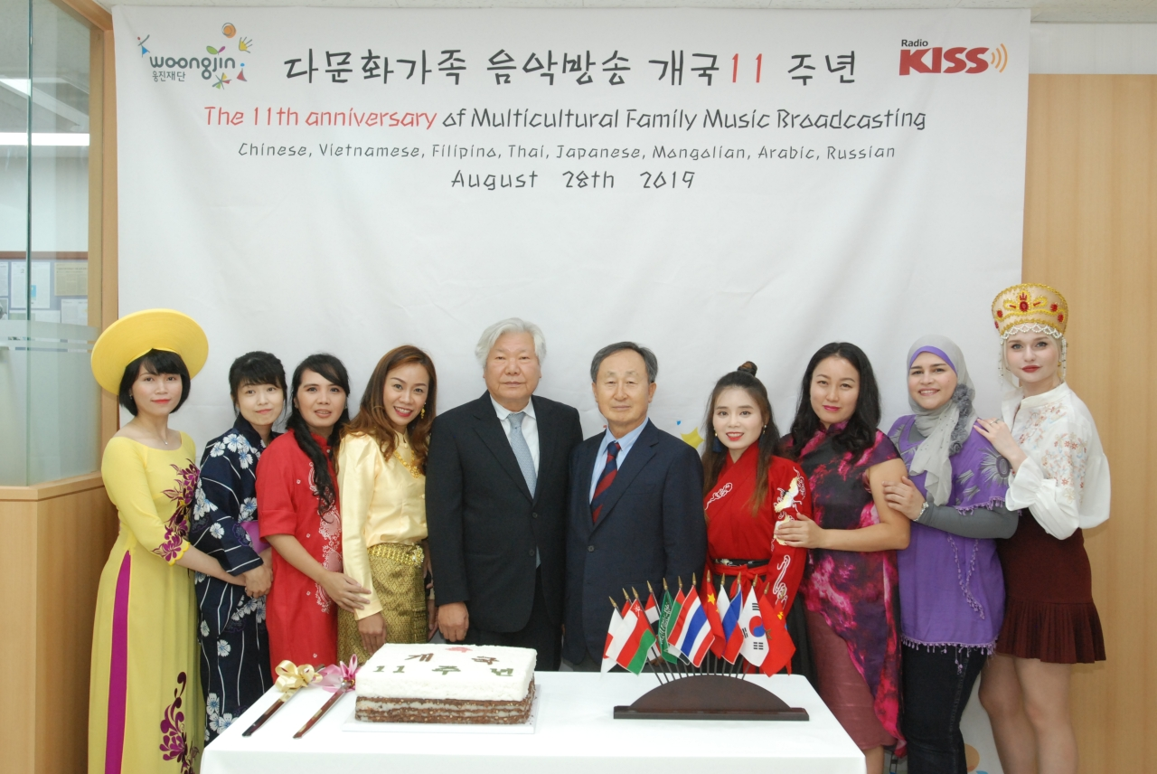 Hosts of the Multicultural Family Music Broadcasting Service pose for photo with Woongjin Foundation Chairman Shin Hyun-woong and cable network Digital Skynet President Kim Choong-hyun (center) at the 11th anniversary event on Wednesday. (Woongjin)