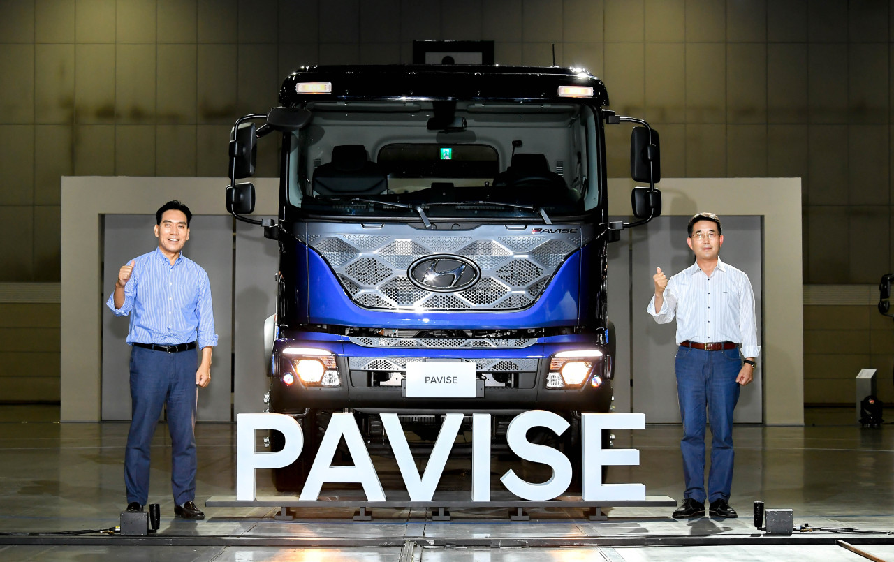 Lim Chung-hwan (left), Hyundai Motor Group's vice president and head of Commercial Vehicle Development Center 2 and Lee In-Cheol, vice president and head of Commercial Vehicle Business Division, pose with Pavise during the Hyundai Truck & Bus Business fair in Ilsan, Thursday. (Hyundai Motor Group)