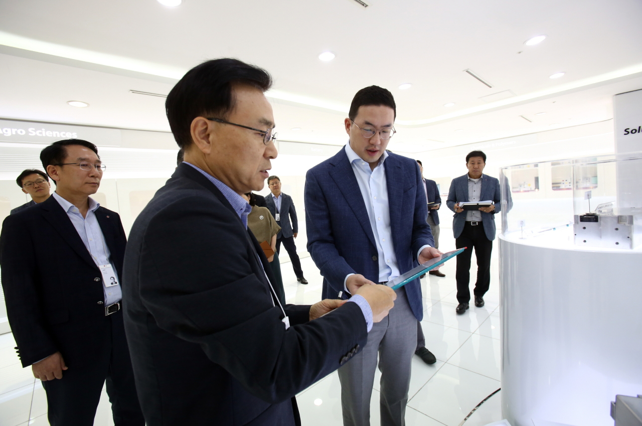 LG Chairman Koo Kwang-mo (right) looks at the third-generation battery pack developed by LG Chem for long-range electric vehicles, at the battery maker's R&D unit in Daejeon on Thursday. With the new battery pack, electric vehicles are capable of running more than 500 kilometers on a single charge. (LG Group)