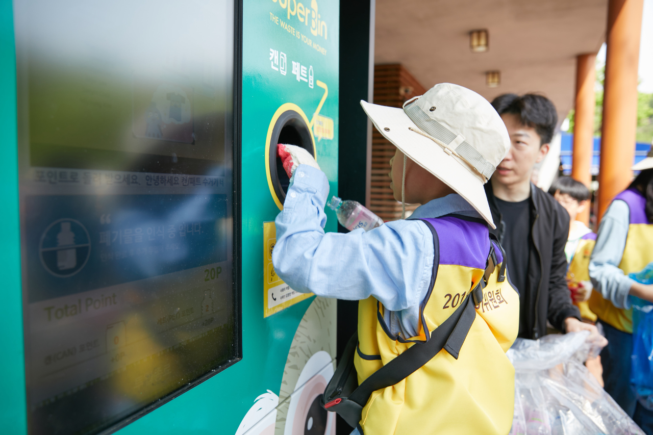 SuperBin customers recycle plastic bottles in Seoul with the reverse vending machine Nephron. (SuperBin)