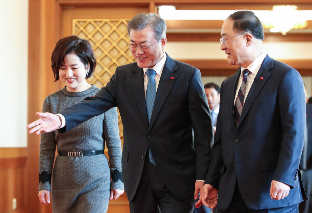 President Moon Jae-in (center) walks with Deputy Prime Minister for the Economy Hong Nam-ki (right) at Cheong Wa Dae on Dec. 10, when the latter was appointed to the post. (Yonhap)
