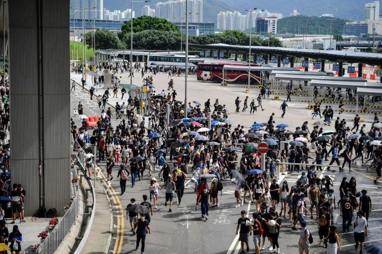 Protesters run from police at the bus terminal at Hong Kong's airport on Sunday. (AFP)