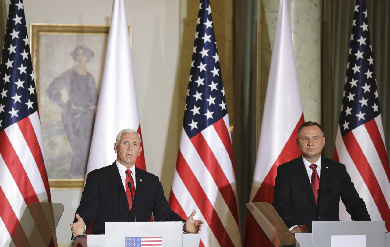 US Vice President Mike Pence gestures next to Polish President Andrzej Duda, right, during press statements after their meeting in Warsaw, Poland, Monday. (AP-Yonhap)