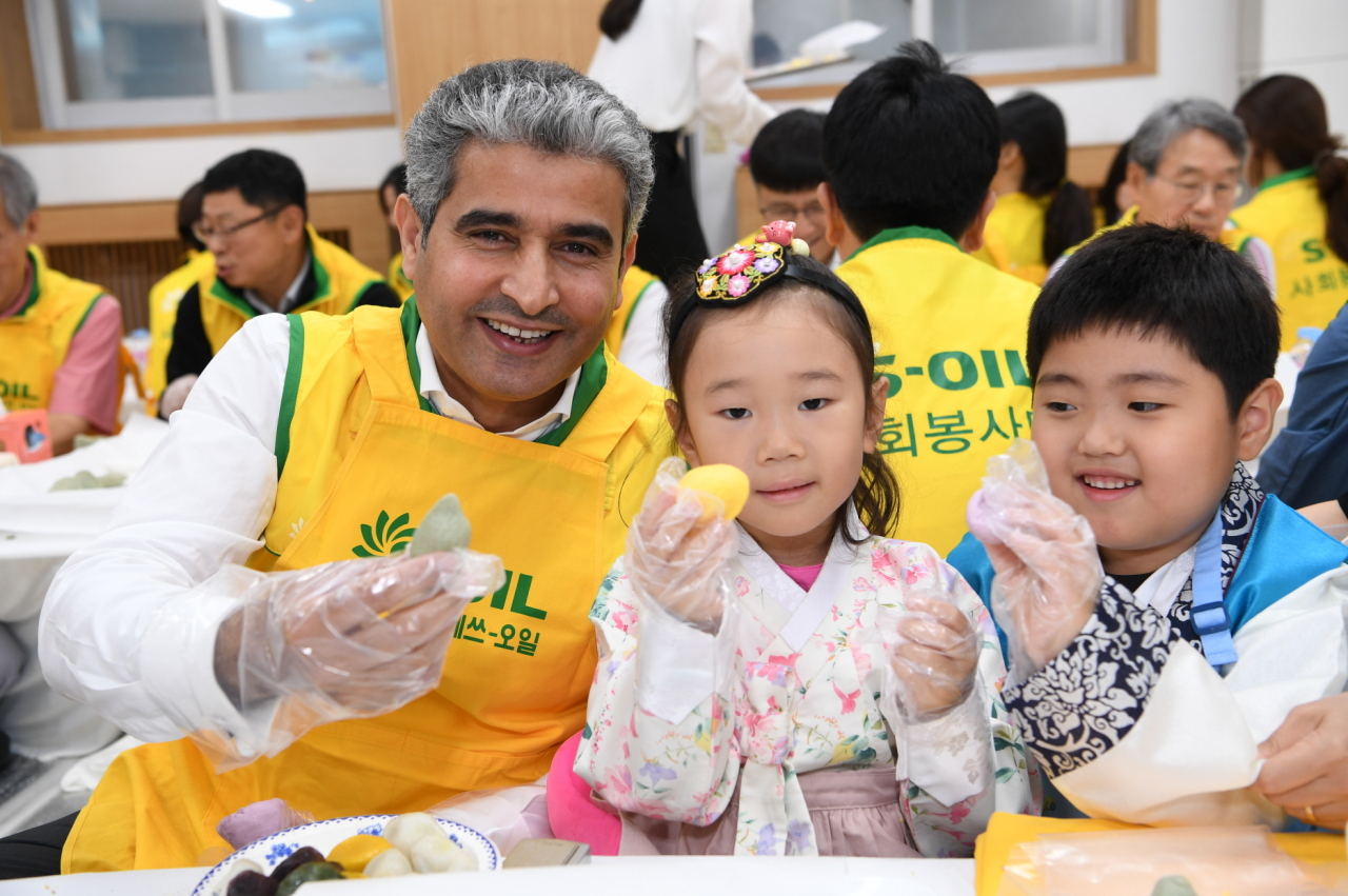 S-Oil CEO Hussain A Al-Qahtani (left) makes songpyeon with children during a charity event in Seoul on Wednesday. (S-Oil)