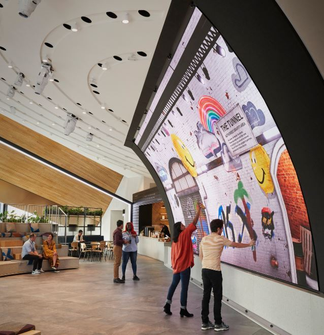 Visitors draw pictures on a curved LED screen at Samsung KX in Coal Drops Yard in London on Tuesday. (Samsung Electronics)
