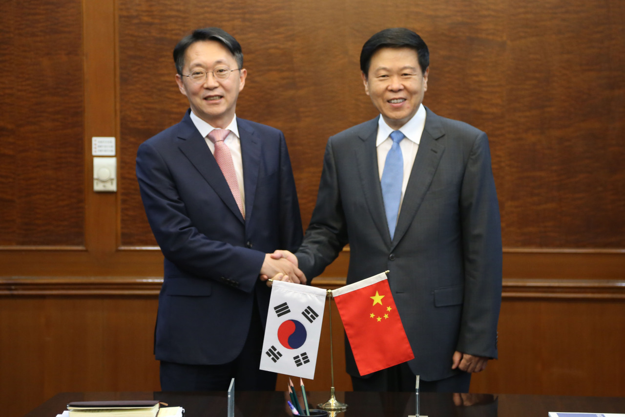 National Tax Service Commissioner Kim Hyun-jun (left) and his Chinese counterpart Wang Jun in Beijing shakes hand after signing an advance pricing arrangement in Beijing, China, on Sept. 4, 2019 (Yonhap)