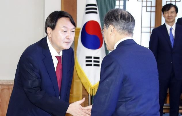 President Moon Jae-in (right) shakes hands with new Prosecutor General Yoon Seok-yeol while then senior presidential secretary Cho Kuk looks on at Cheong Wa Dae in July. (Yonhap)