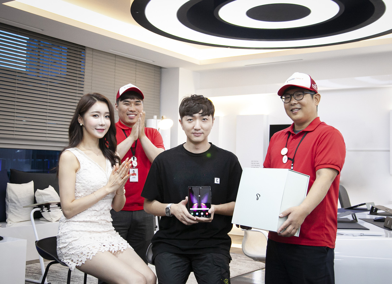 An SK Telecom customer receives the Galaxy Fold on Friday as part of the mobile carrier's event to deliver the first foldable device to mark its launch. (SK Telecom)