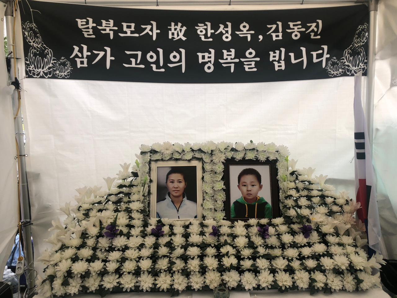 Portraits of Han Sung-ok and Kim Dong-jin are placed at the memorial altar in Gwanghwamun, Seoul, on Sept. 2. (Jo He-rim/The Korea Herald)