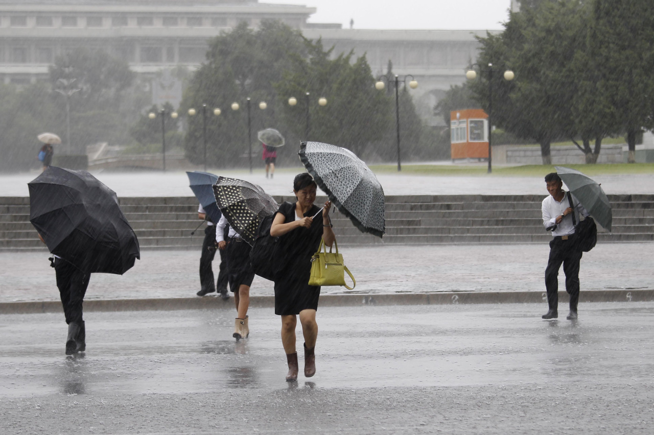 Pedestrians shield themselves from wind and rain brought by Typhoon Lingling Saturday, in Pyongyang, North Korea. (AP-Yonhap)