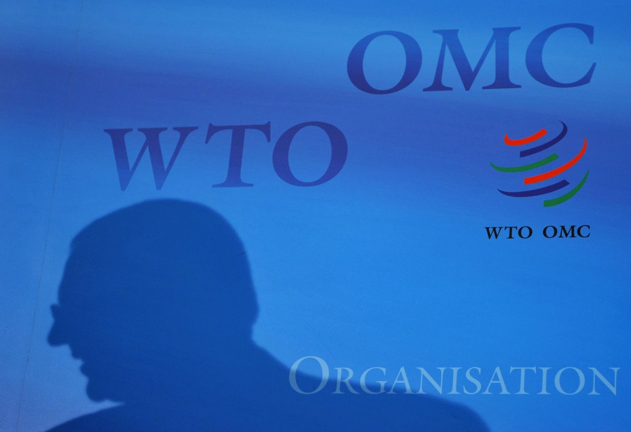 A silhouette of an official is seen with the logo of the WTO in the background at the organization headquarters in Geneva, on July 21, 2008. (AFP)