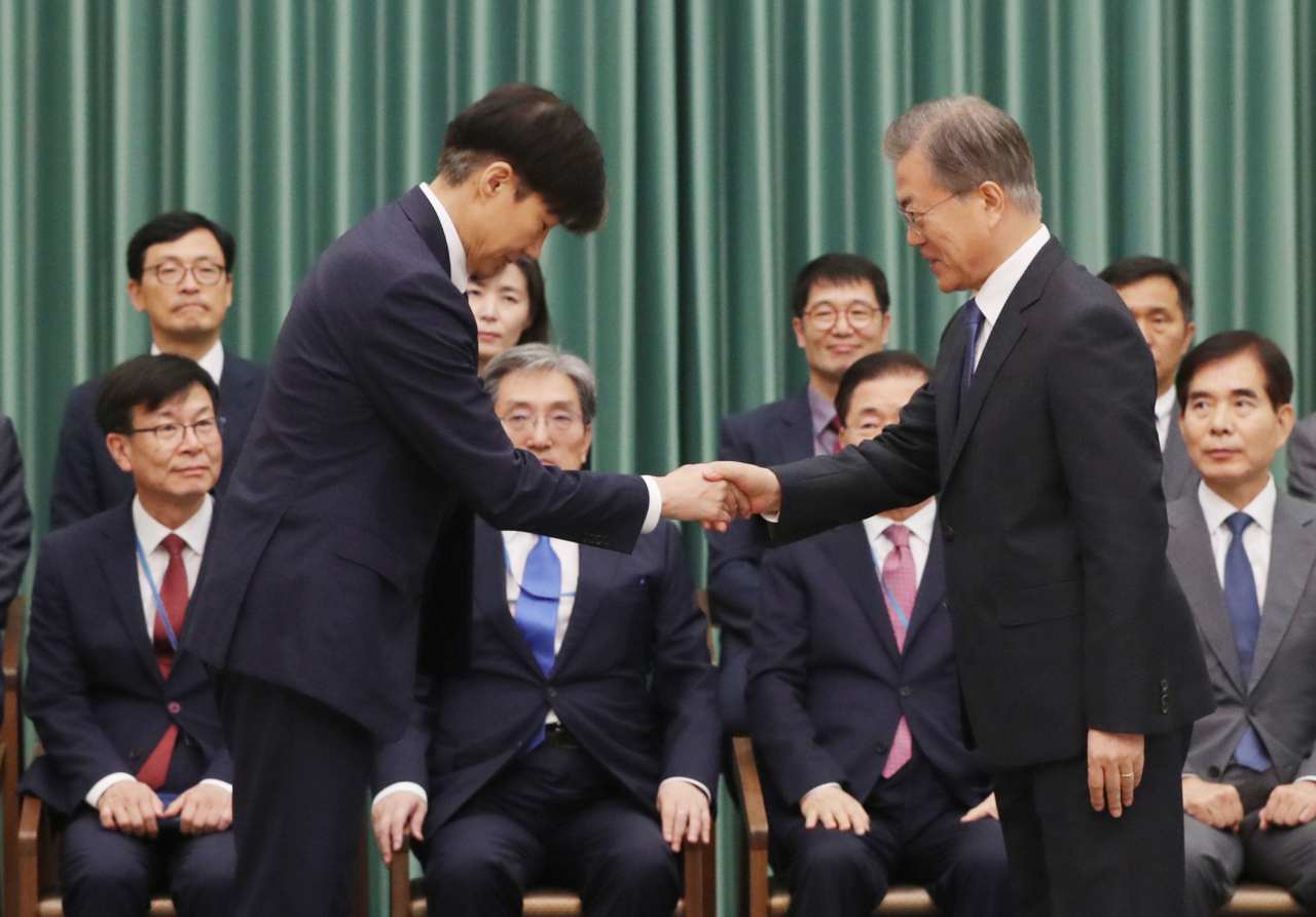President Moon Jae-in (right) shakes hand with new Justice Minister Cho Kuk after giving him a letter of appointment at Cheong Wa Dae in Seoul on Monday. (Yonhap)