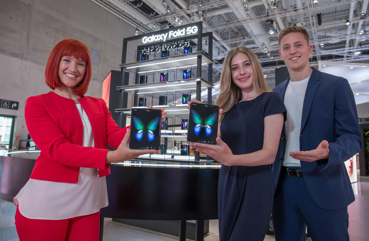 IFA officials hold up the Galaxy Fold devices at Samsung Electronics' exhibition hall at IFA2019 in Berlin. (Samsung Electronics)