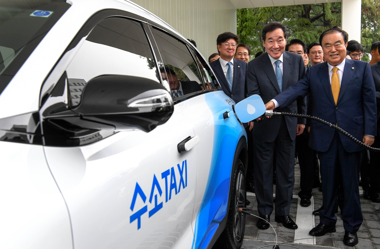 Prime Minister Lee Nak-yon (center) and National Assembly Speaker Moon Hee-sang (right) pose on Tuesday while hydrogen-charging a fuel cell electric taxi at the world's first hydrogen station built in the middle of the parliament in Seoul. (Hyundai Motor)