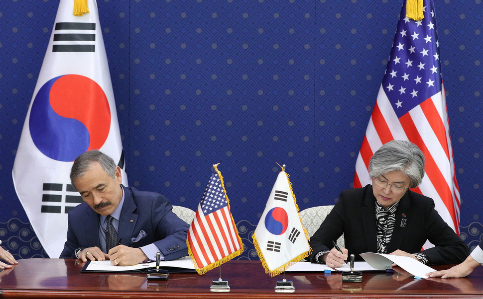 South Korean Foreign Minister Kang Kyung-wha and US Ambassador to South Korea Harry Harris sign a South Korea-US defense cost-sharing agreement at the Ministry of Foreign Affairs on Mar. 8. (Yonhap)