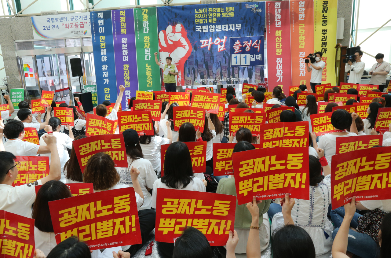 "Health workers picket outside the National Cancer Center in Ilsan, north of Seoul, Monday, with signs reading, ""Root out free labor!"" (Yonhap)"