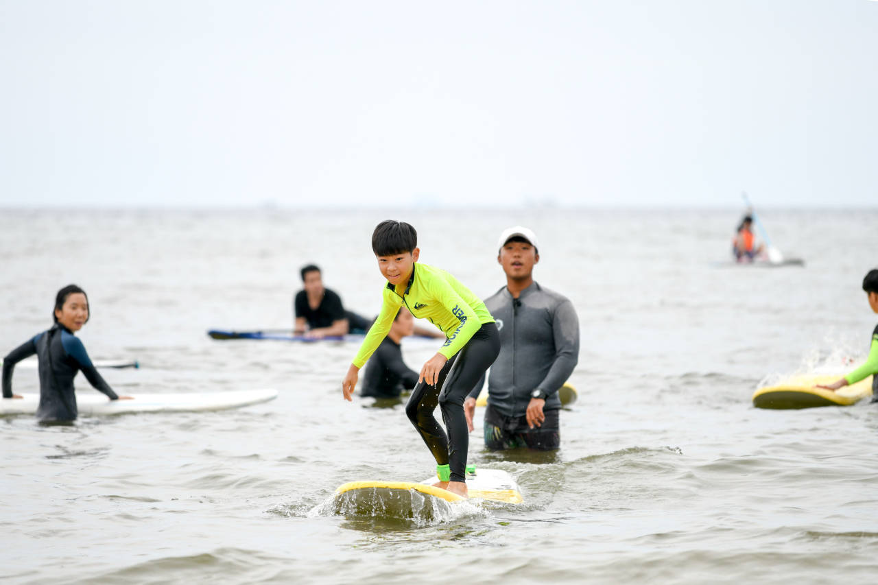 Surfing is a popular activity at Iho Tewoo Beach on Jeju Island. (Airbnb)