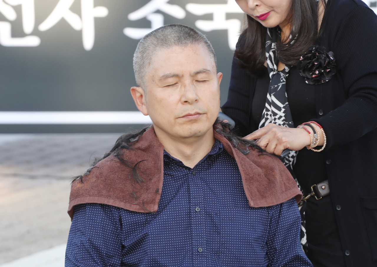 Hwang Kyo-ahn, chairman of the main opposition Liberty Korea Party, has his hair shaved at a plaza in front of Cheong Wa Dae in Seoul on Monday, calling for the resignation of Justice Minister Cho Kuk (Yonhap)