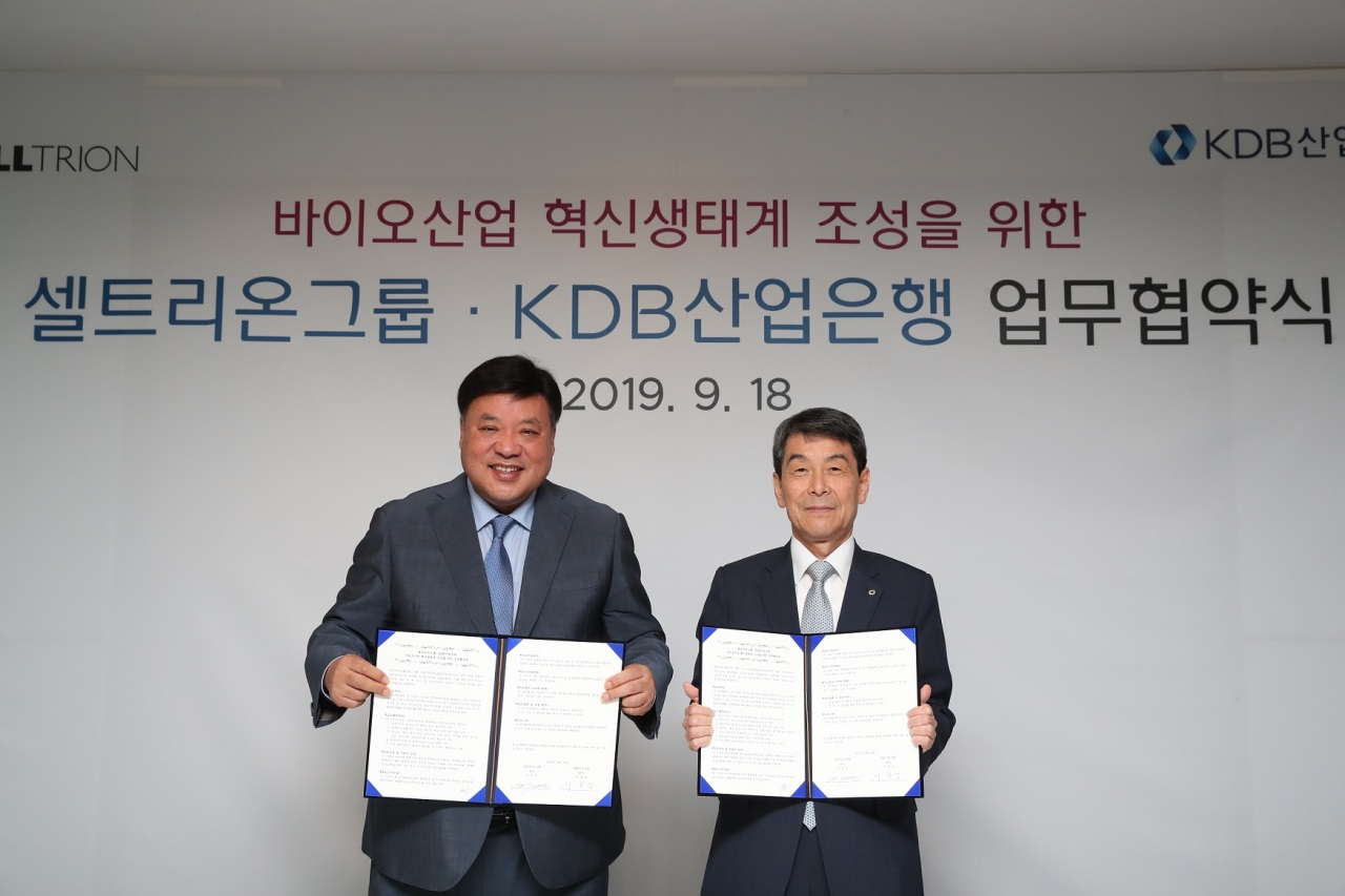Celltrion Chairman Seo Jung-jin (left) and KDB Chairman Lee Dong-gull pose during a memorandum of understanding signing ceremony in Seoul, Wednesday. (Celltrion)