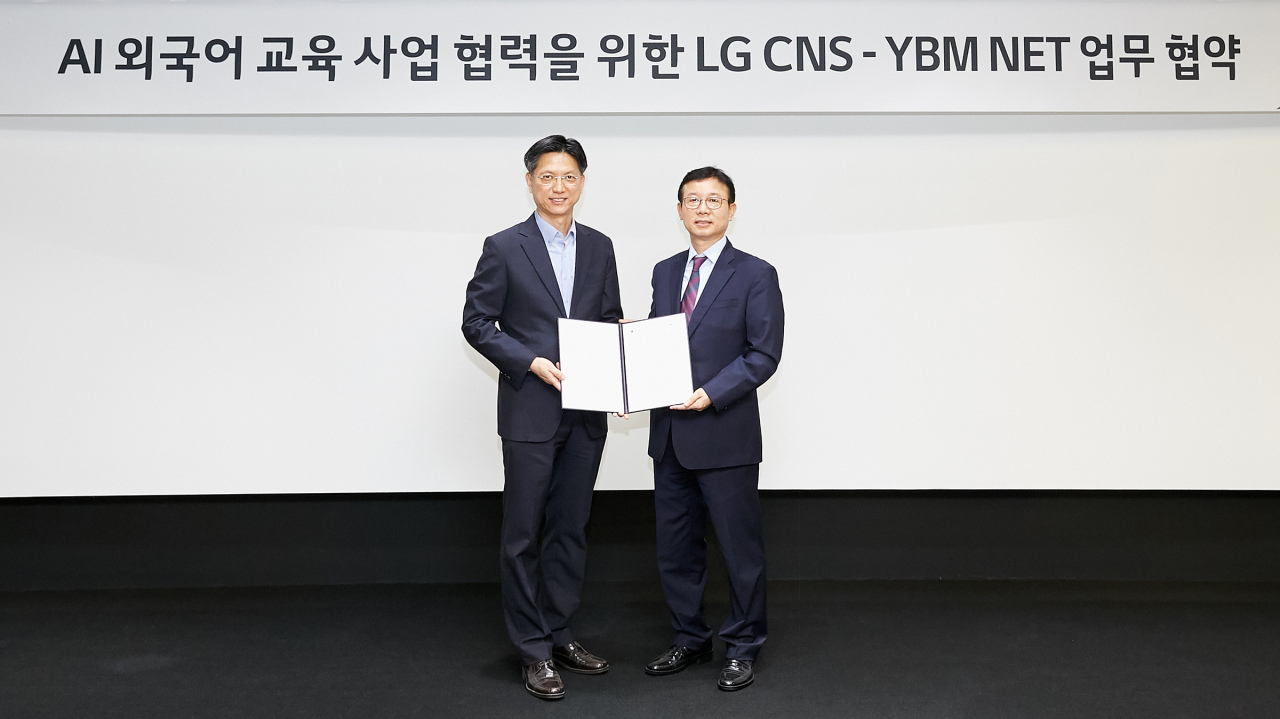 LG CNS customer business department chief Kim Eun-saeng(left) meets with his YBM NET counterpart Wednesday to sign an MOU for foreign-language education app development. LG CNS