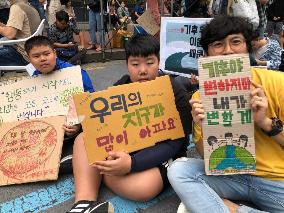 Kim Gi-hun (first from left), who teaches the first graders in middle school, holds a placard reading