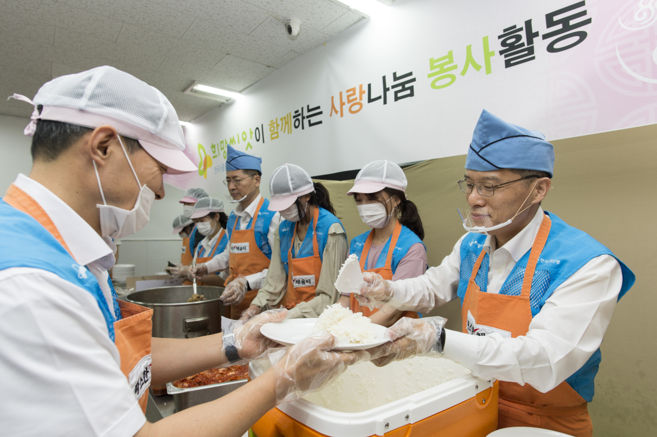 Eximbank Deputy President Kang Seung-joong (right) helps serve meals to the homeless at a soup kitchen near Seoul Station on Sept. 10. (Eximbank)
