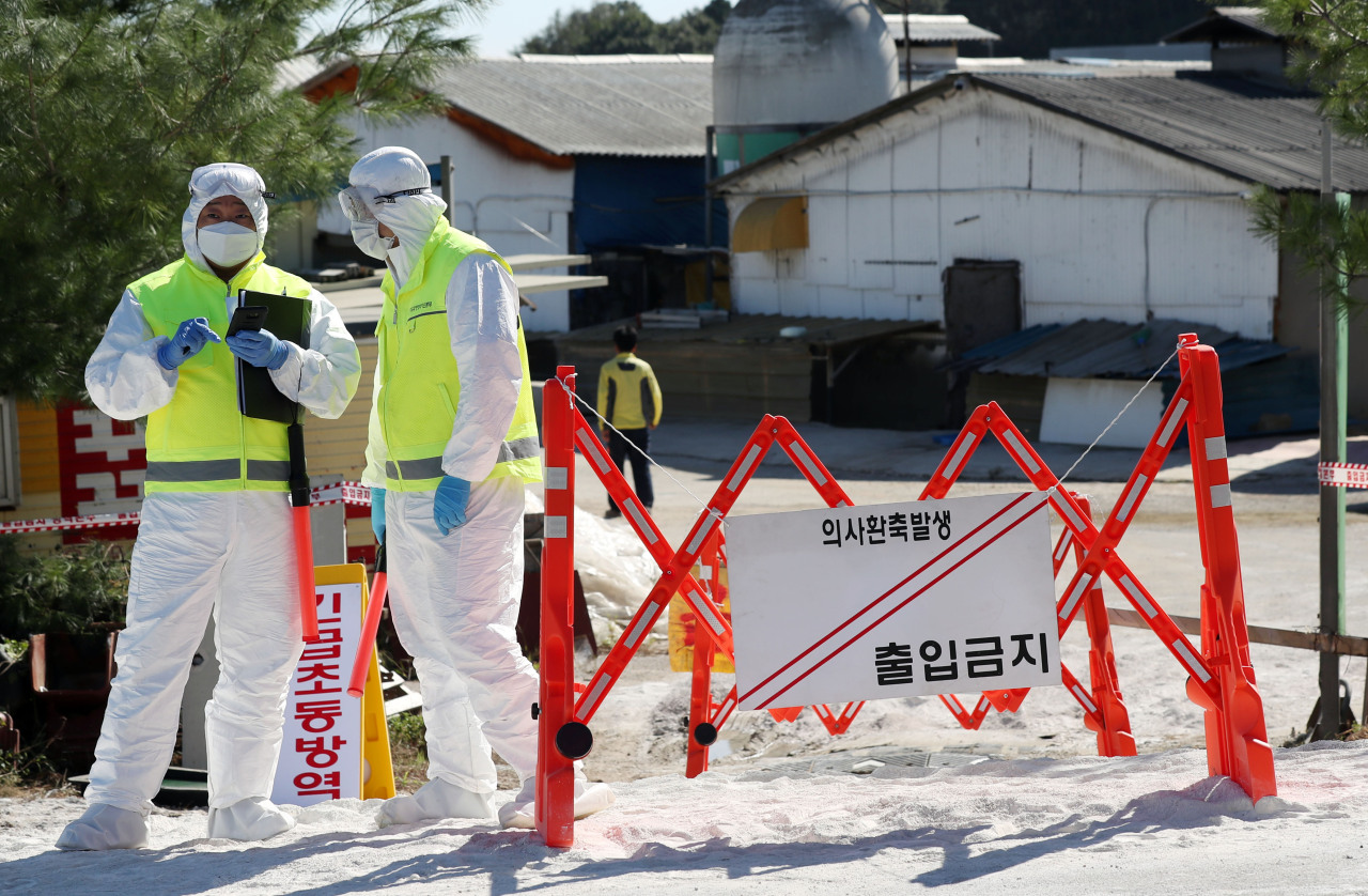 Quarantine officials control access to a pig farm in Gimpo, Monday, after a suspected case of African swine fever was reported in the city early in the day. (Yonhap)