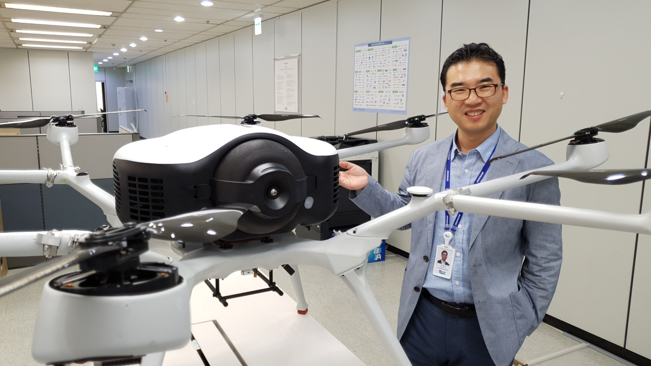 Doosan Mobility Innovation Vice President Lee Chang-seon presents the DS30, hydrogen-powered drone set for world debut next month, in his office in Yongin, Gyeonggi Province. (DMI)