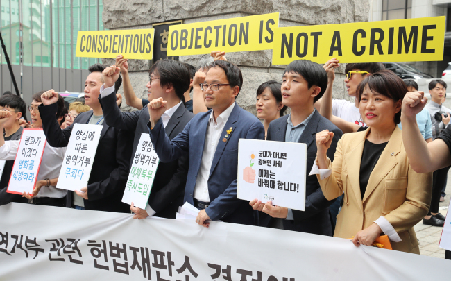 Activists and conscientious objectors are seen outside the Constitutional Court in Seoul on June 28, 2018. (Yonhap)