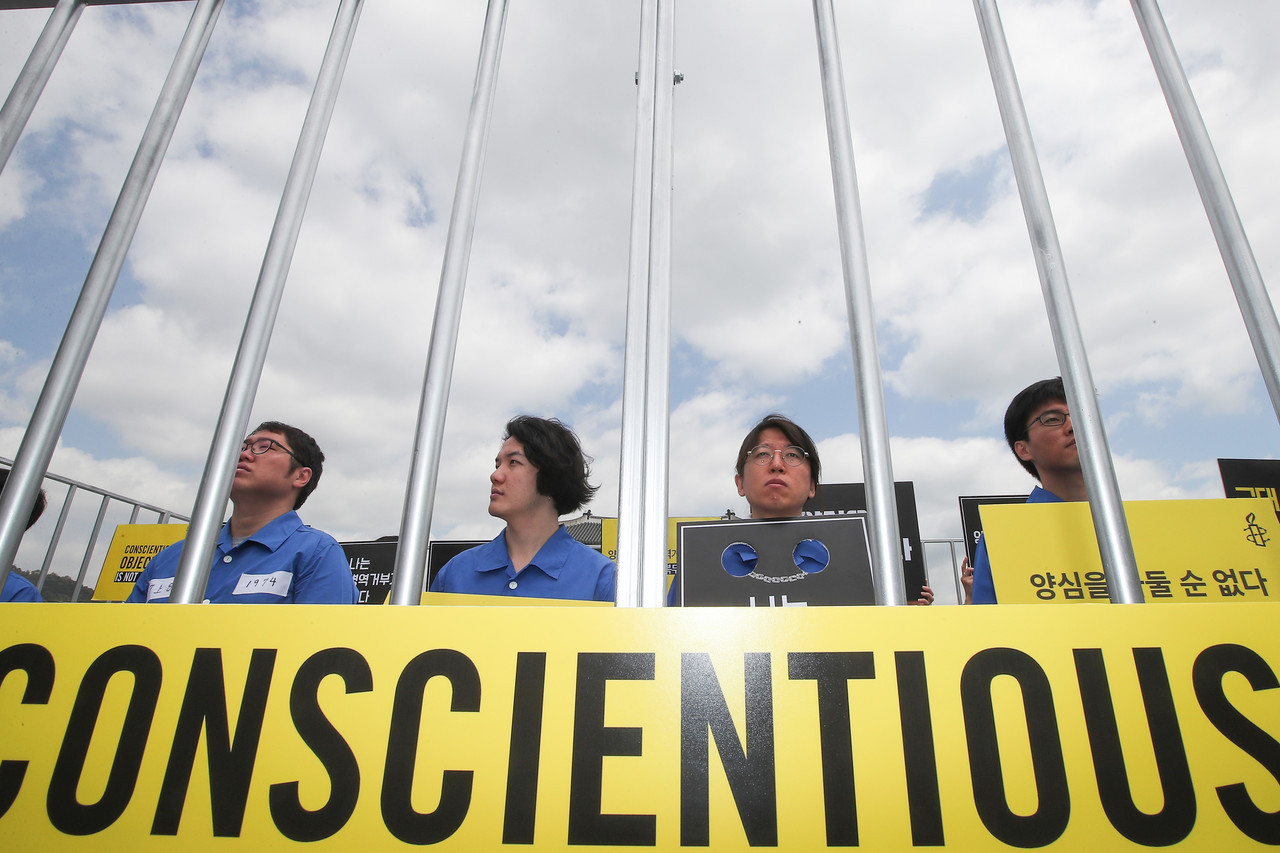 Protesters demanded the government not punish conscientious objectors and introduce alternative service options for them in observance of the International Conscientious Objectors Day in May 2017. (Yonhap)